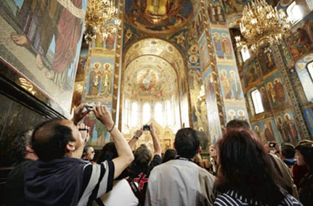 Play video icon, Tourist taking pictures inside a church in St. Petersburg Russia