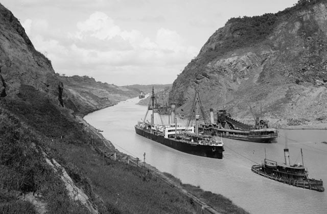 A black and white picture of cargo ships and tug boats in the Panama Canal