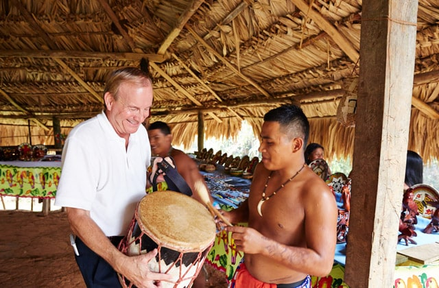 A man holding a drum, talking to a native of the Embera tribe