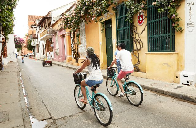 2 people riding colorful bikes on a small street next to colorful houses covered with flowers cascading from the rooftops
