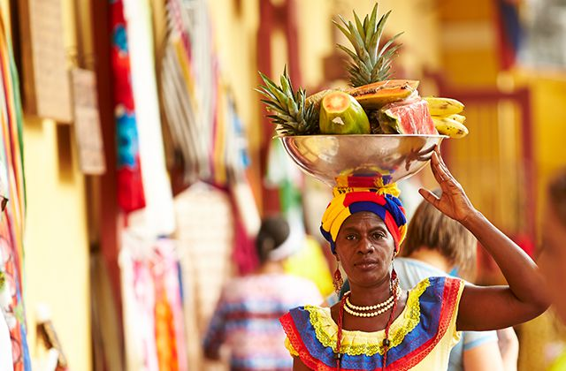 A woman dressed in colorful, native attire balancing a bowl of fruit on her head