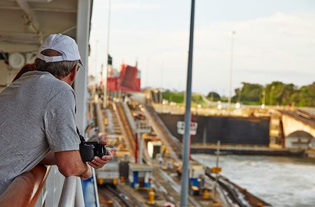 Man leaning over the railing of a ship, holding his camera, viewing the locks of the Panama Canal
