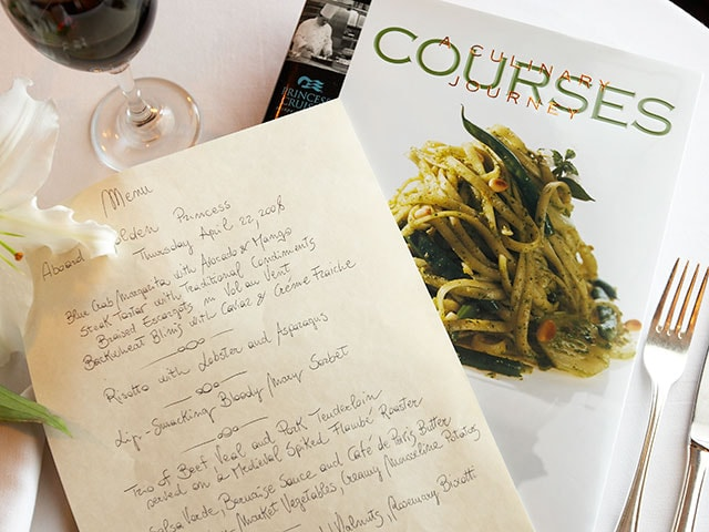 "A book on table ""Courses: A Culinary Journey"" with a handwritten note"