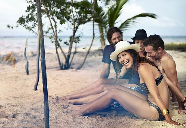 group of four friends sitting under palm tree, enjoying time on beach together