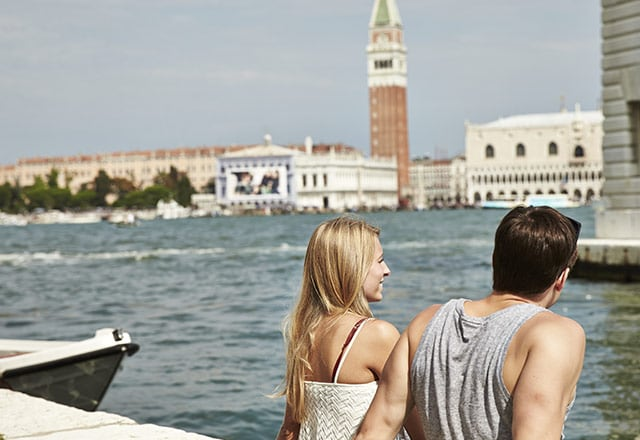 couple sits together looking over the Grand Canal in Venice, Italy