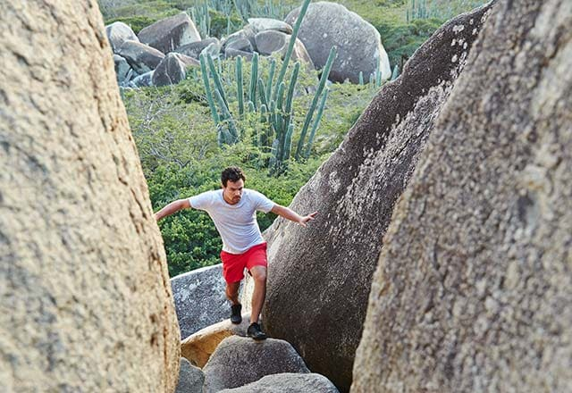young man exploring the Ayo & Casibari Rock Formations in Aruba