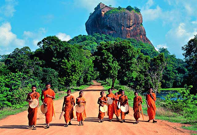 children walking down road in Sri Lanka with Lion Rock in the background
