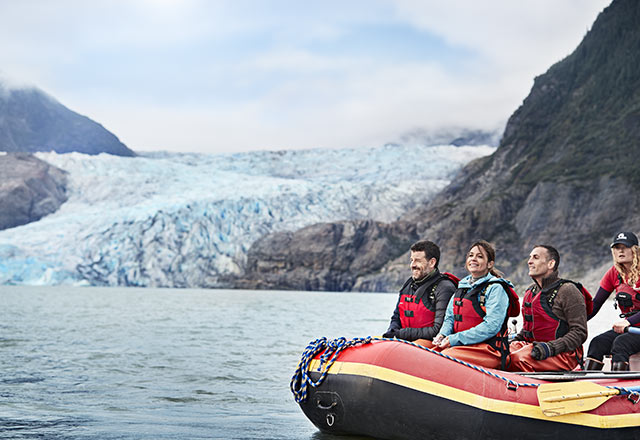 people on raft in bay surrounded by glaciers