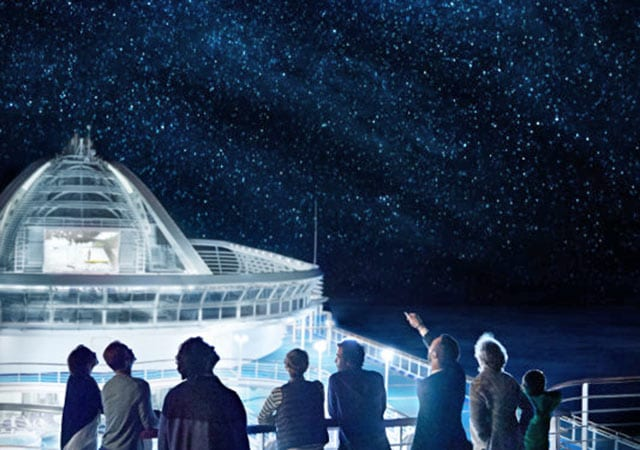 Passengers on top deck of a Princess Cruise ship looking at a star filled night sky