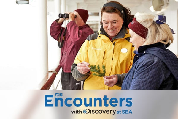 Encounters with Discovery at Sea logo; Ship employee in yellow jacket showing guest a native plant