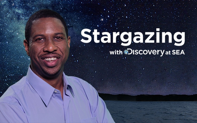 Stargazing with Discovery at Sea logo. Astrophysicist Dr. Hakeem Oluseyi against a star filled sky