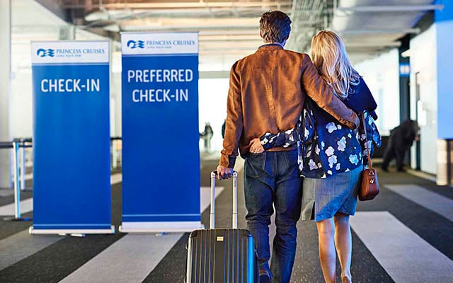 "couple walking in the port draggging a carry-on luggage waking by the ""check in"" and ""Preferred check-in"". Priority Embark and Debark"