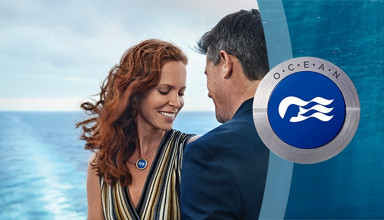 An attractive couple smiling on the deck of a cruise ship with the open seas in front of them.