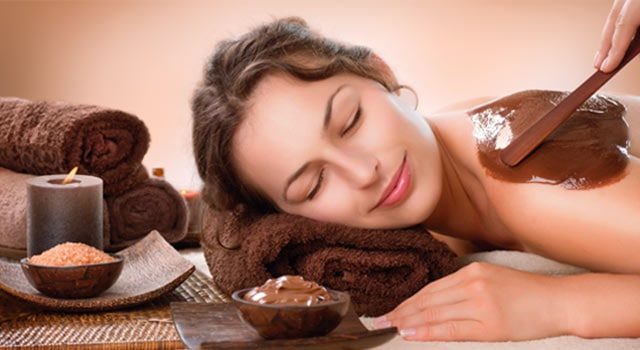 Woman laying on her front with her head resting on a folded towel, being painted with chocolate