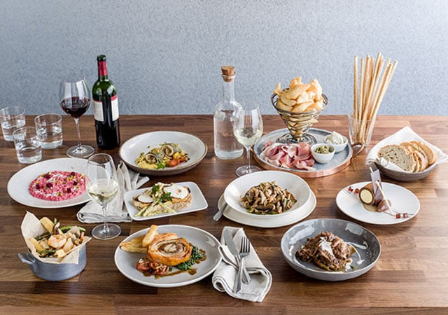 Dishes with food, and glasses of wine and water from the new Sabatinis Trattoria