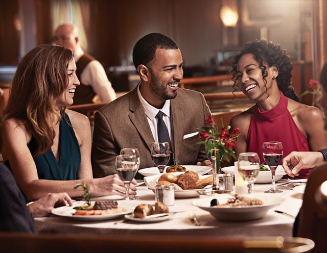 Three people sitting at a table with plates of food and glasses of wine