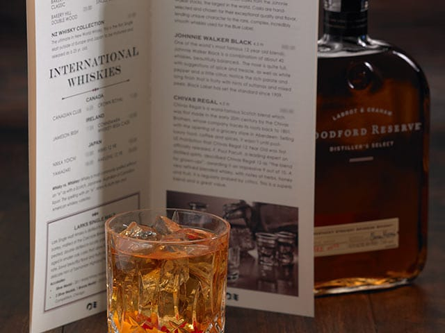 Glass of whiskey, on the rocks, in front of whiskey menu with Woodford Reserve Whiskey bottle