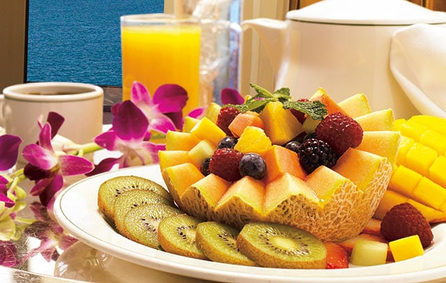A plate of fruits, with a glass of orange juice, and cup of coffee, decorated with a flower lei