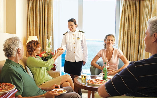 Server delivering food to stateroom with four people, sitting in chairs