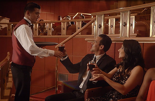 Woman and man sitting in a theatre, being given wine by a male server