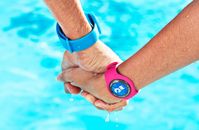 Mans hand, with blue watch band holding woman's hand wearing pink watch band with blue Ocean Medallion with white seawitch logo