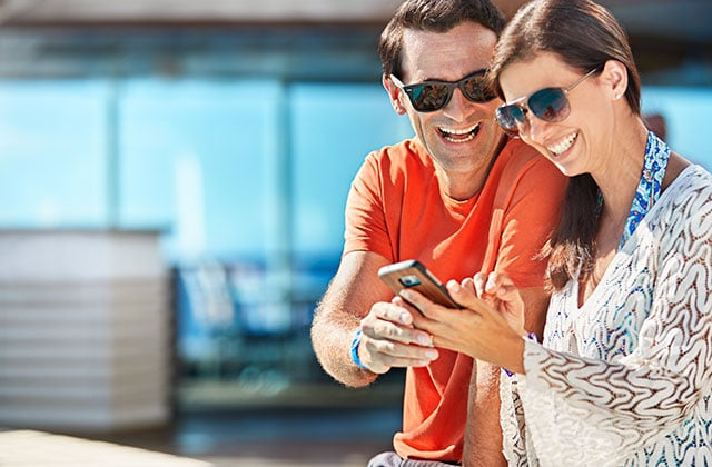 Man and woman wearing sunglasses looking at mobile phone