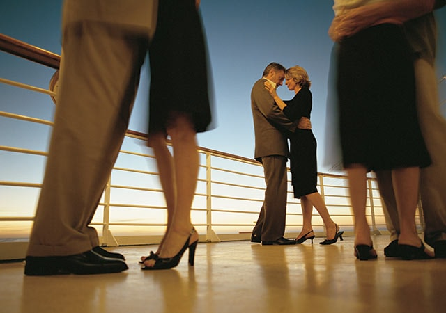 Couples dressed in formal wear, dancing on deck in the evening.