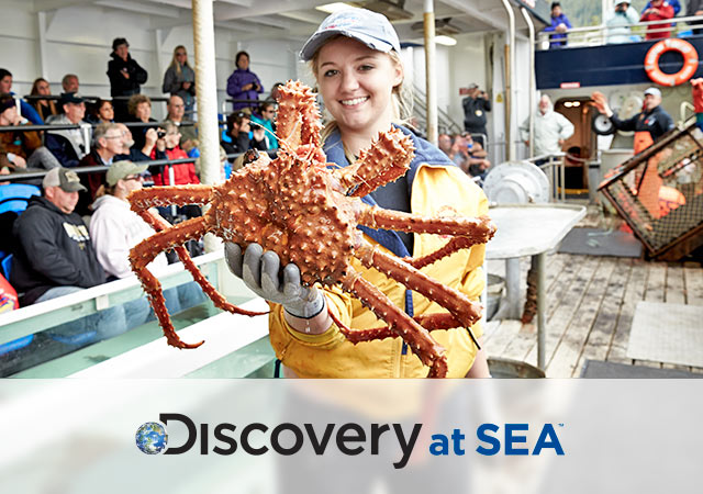 Discovery at Sea logo; Woman holding spider crab