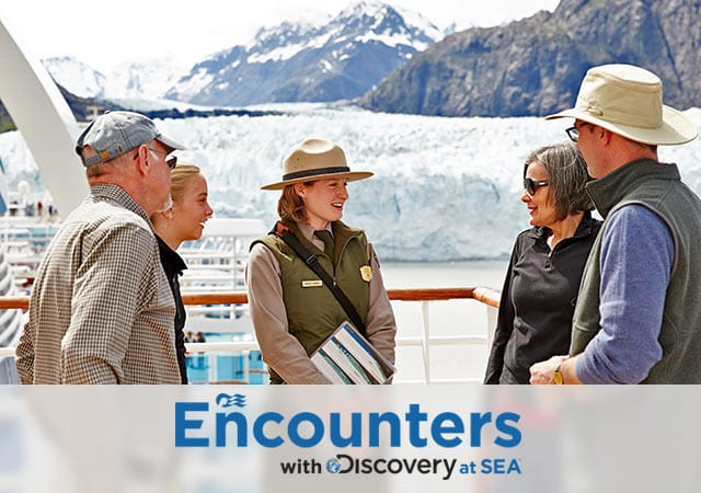 Encounters with Discovery at Sea logo; Alaska ranger talking to four guests onboard a Princess ship in front of snow capped glaciers.