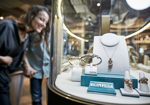 Fine jewelry featured in a case with Effy logo; woman looking at jewelry in background