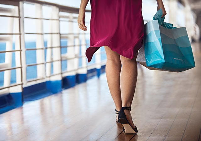 Bottom half of woman walking on deck, holding two paper shopping bags
