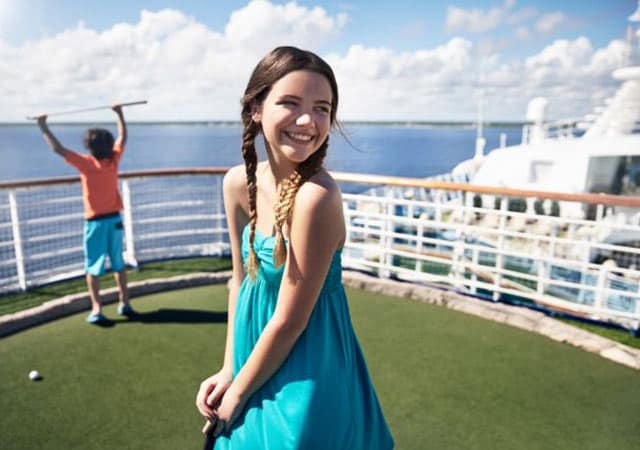 girl standing on mini golf course posing with golf club, boy in background holding golf club in the air while looking out at the ocean