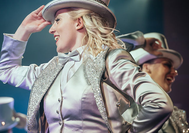 Woman in silver suit with top hat