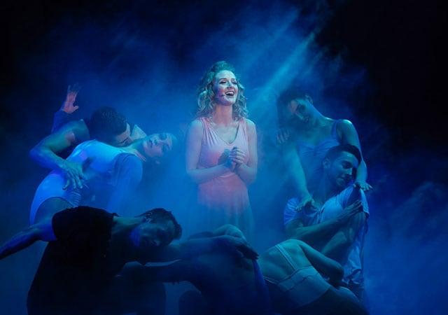 Seven dancers surrounding one female singer