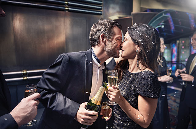 couple ringing in the new year with a kiss on a princess ship
