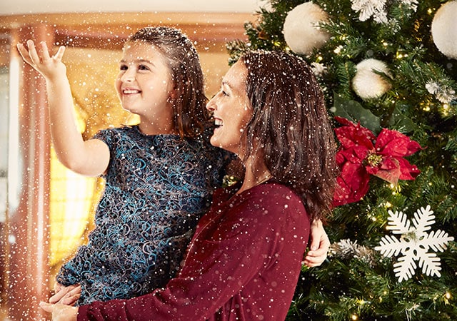 mother holds daughter in front of a decorated Christmas tree. Daughter throws artificial snow in the air.