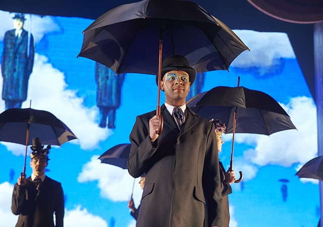 Men wearing trench coats holding umbrellas as part of Magic to Do