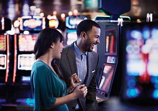 couple enjoying the slot machines in the vegas-style casino