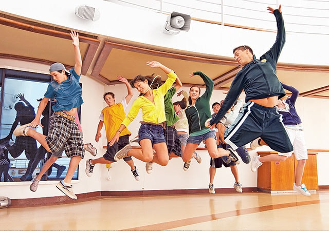 group of teens jumping in unison with feet off the ground and hands raised above heads, practicing a dance move as demonstrated by instructor.