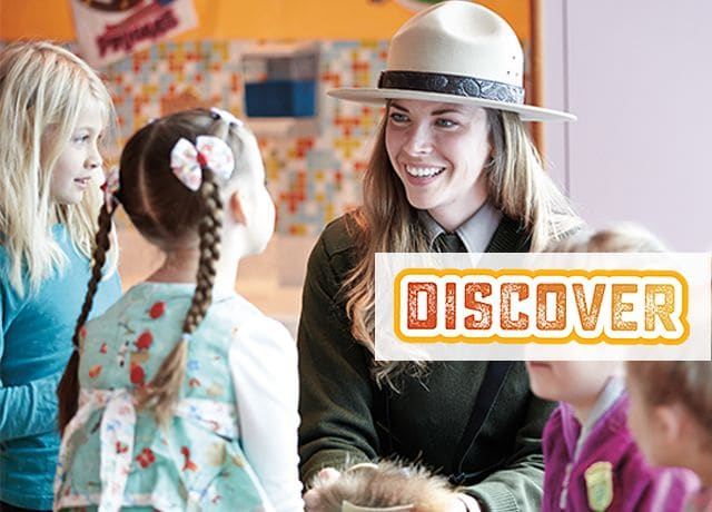 Discover logo; Alaska ranger talking to four young girls