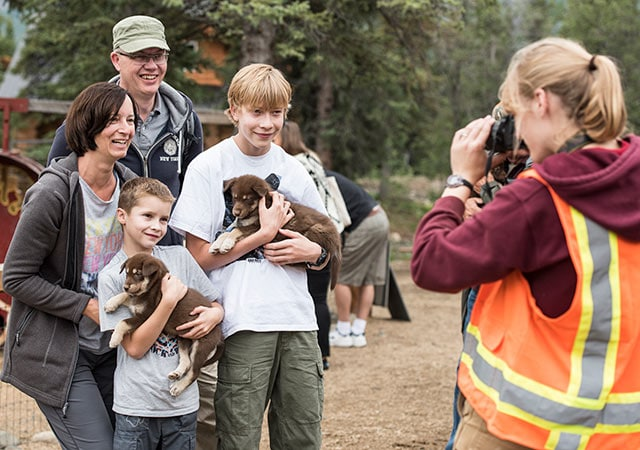 family having their photo taken while holding sled-dog puppies in Alaska.