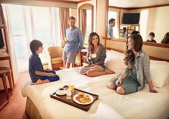 Family of four enjoying breakfast together in their stateroom.