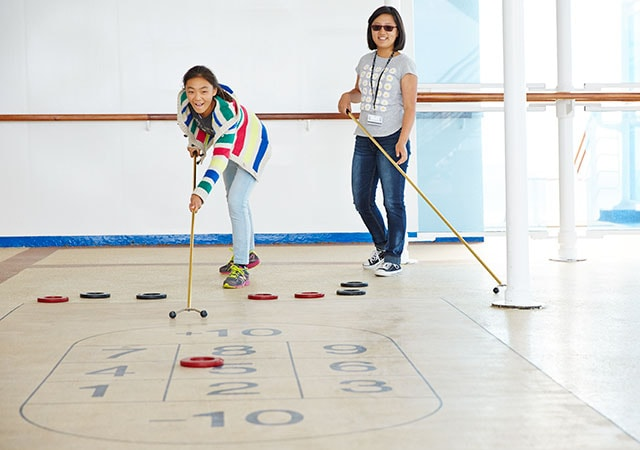 Shuffleboard court 10, 1, 2, 3, 4, 5, 6, 7, 8, 9, 10. mother and daughter play shuffleboard. daughter lands her disc on the number 5.