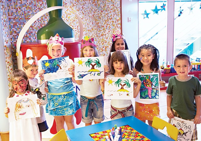 group of children in the Youth Center standing together and proudly showing the artwork they've created.