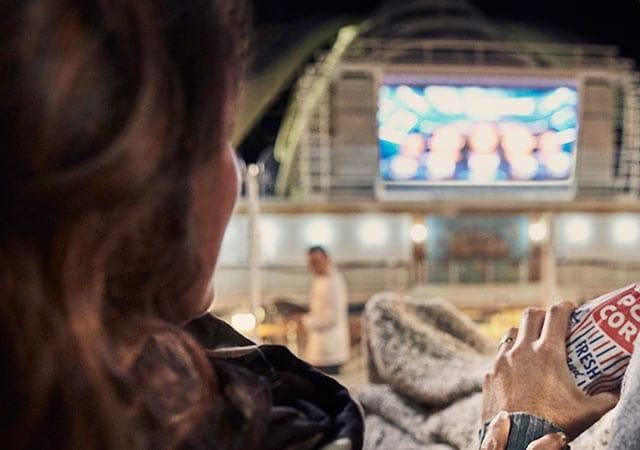 Mujer, mano de un hombre sosteniendo una bolsa de palomitas de maíz con la palabra Fresh, mientras ve la pantalla de cine gigante al aire libre