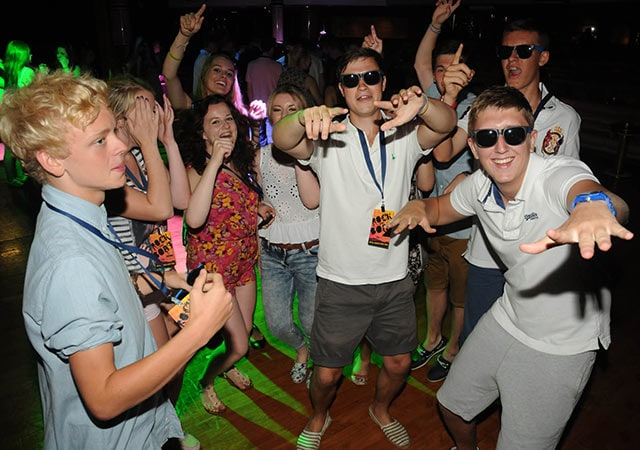 mixed group of teenagers standing in a half-circle on dance floor, dancing at night club