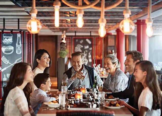 Familia feliz compartiendo una comida en Plank's BBQ