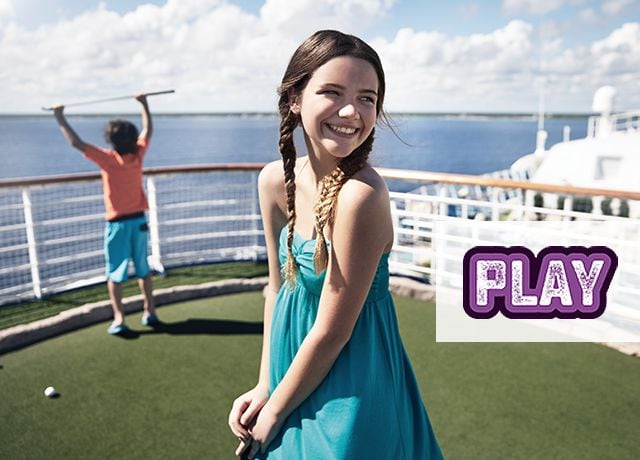 Play logo; girl standing on mini golf course posing with golf club, boy in background holding golf club in the air while looking out at the ocean