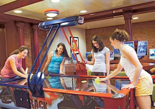 Girls playing air hockey against each other while their friends watch and cheer them on.