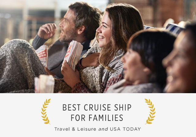 Family sitting in lounge chairs, holding bags that say popcorn. Accolade: Best Cruise Ship for Families, Travel & Leisure and USA Today